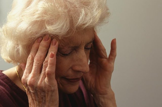 senior woman holding her head